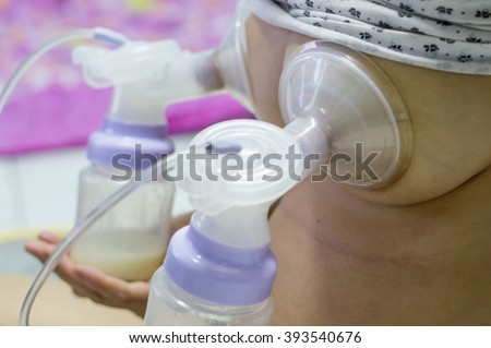 Mother pumped breast milk from the breast, Store for her child - stock photo