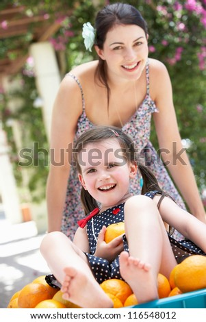 Mother Pushing Daughter In Wheelbarrow Filled With Oranges - stock photo