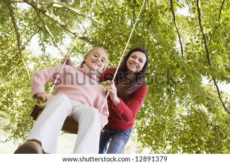 Mother pushing daughter on garden swing - stock photo