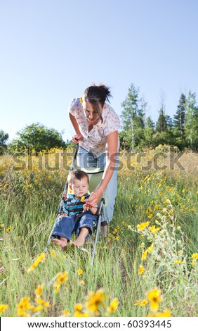 Mother pushing her baby son in a stroller offering him a flower to play with - stock photo