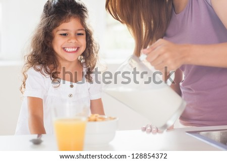 Mother putting milk in the cereal of his daughter in kitchen - stock photo