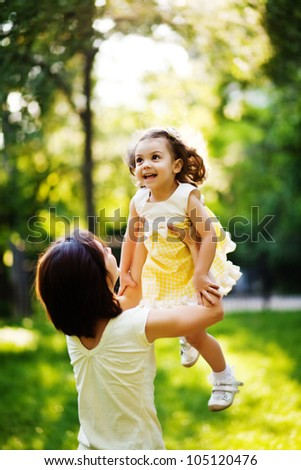 Mother raising her little daughter up high - stock photo