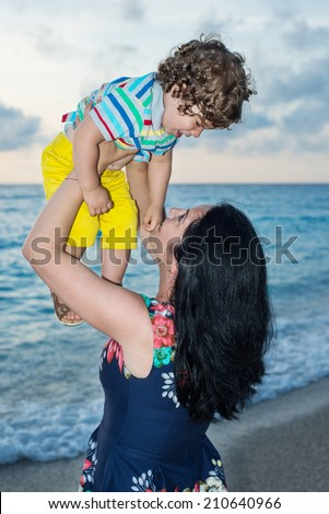 Mother raising up to the sky her toddler boy on the beach - stock photo