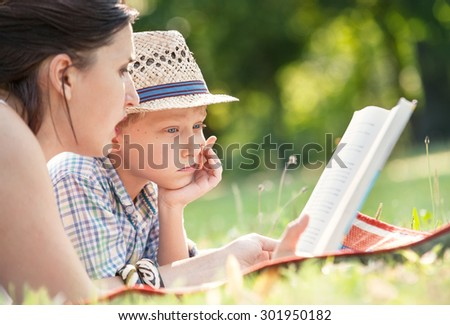 Mother read a tales for her son in summer garden - stock photo