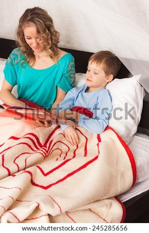 Mother reading a book to her child before sleep - stock photo