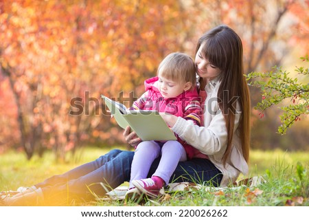 mother reading a book to kid outdoors in autumn - stock photo