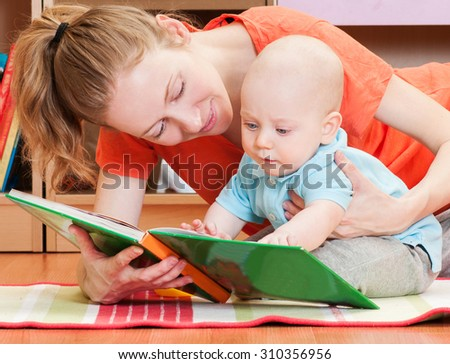 Mother reading a book to little baby son. Indoors - stock photo