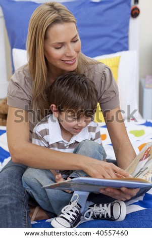 Mother reading a book with her son in bedroom