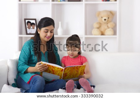 Mother reading a storybook to daughter - stock photo