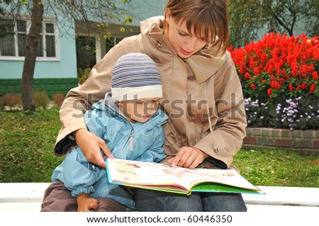 mother reading book in the fall park with her kid
