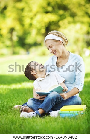Mother reading book to her son and sitting in the park - stock photo