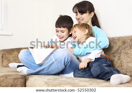 mother reading book to her sons; indoor - stock photo