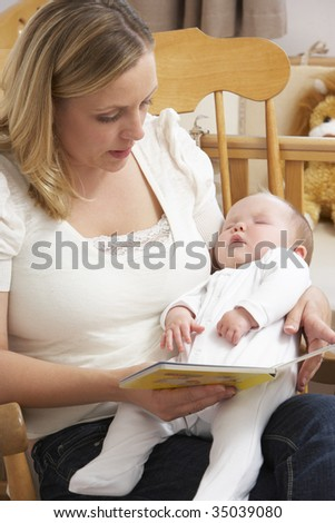 Mother Reading Story To Baby In Nursery - stock photo