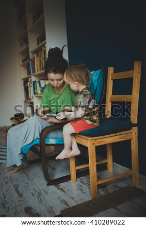 Mother reading with her son at home, casual, real interior, blue wall, lifestyle, toning