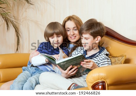 mother reads to children's book - stock photo