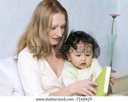 Mother reads to the child the book. - stock photo