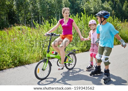 Mother rides bicycle and her children ride rollers on sunny day in park