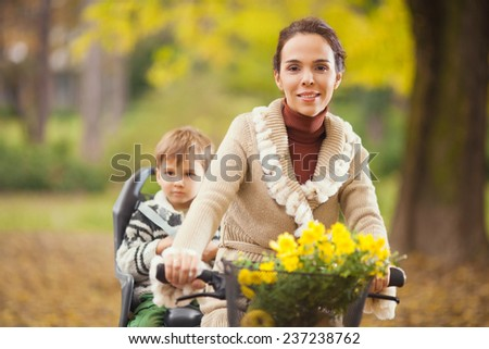 Mother riding a bicycle with her son sitting on the rear bike rack - stock photo