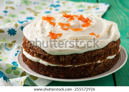 Mother's day carrot cake, homemade moist and sweet layer cake with grated carrot,  walnuts and dried apricot topped with swirls cream cheese frosting.  Delicious delight for holiday - stock photo