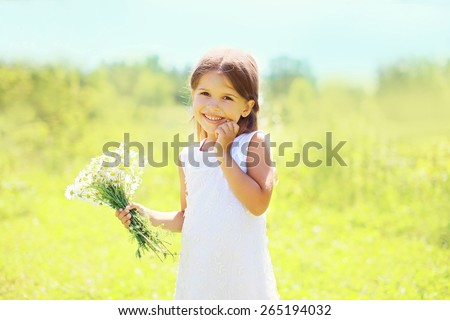 Mother's day, childhood and nature concept - portrait of happy smiling little girl with flowers in sunny summer field