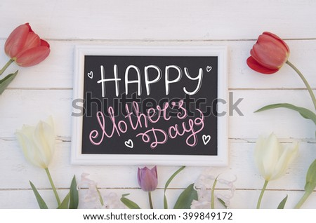 Mother's Day greeting concept. Beautiful tulips and frame with hand lettered inscription on the rustic wooden background. - stock photo