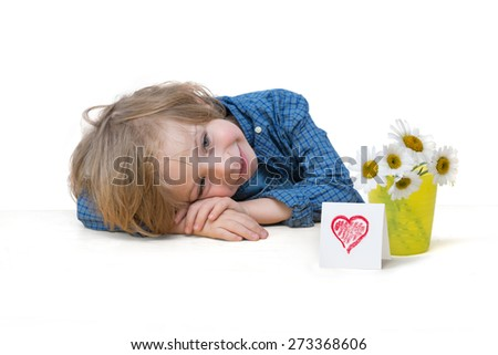 Mother's day greetings. Adorable little boy with blonde hair, blue eyes, smiling, with daisy bouquet and a red heart card on the white table edge isolated over white background - stock photo