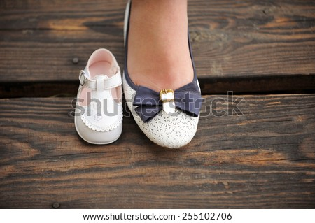 mother's foot in shoe and baby's shoe - stock photo