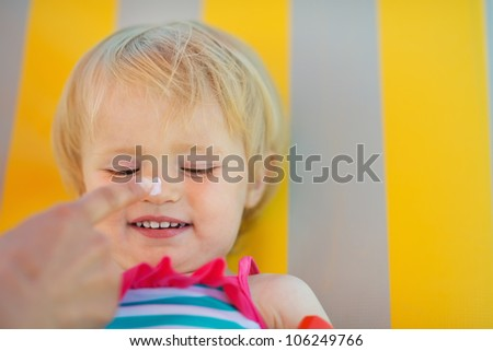 Mother's hand applying sun block creme on baby nose - stock photo