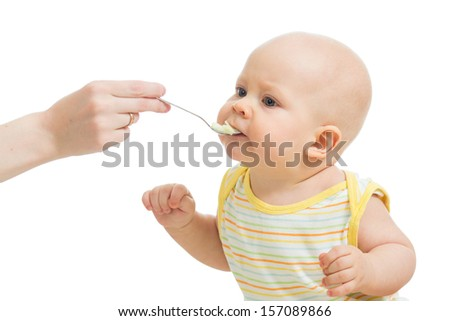 Mother's hand feeding baby with a spoon - stock photo