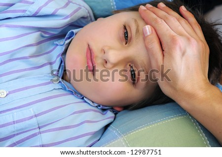 Mother's hand feeling the forehead of a sick child - stock photo