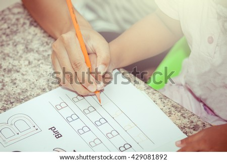 Mother's hand holding child hand writing her homework with crayon,vintage color filter - stock photo