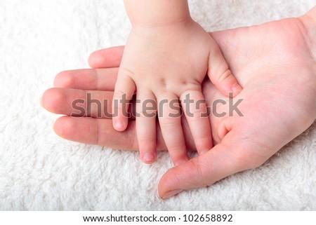 Mother's hand holding newborn baby's hand - stock photo