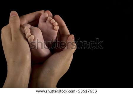 Mother's hands cradling his infant son's feet and toes - sepia - stock photo