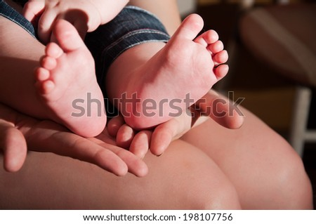 Mother's hands holding her child's feet - stock photo