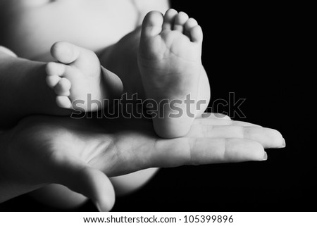 Mother's hands tenderly hold their newborn's feet.