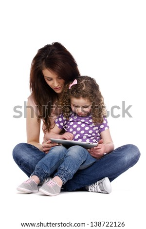 Mother sat with a little girl on her knee playing on a computer tablet isolated on a white background