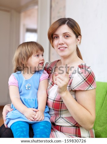 Mother scolds her child in home interior. Focus on woman - stock photo