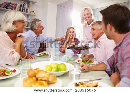 Mother Serves Birthday Cake To Adult Daughter At Family Meal - stock photo
