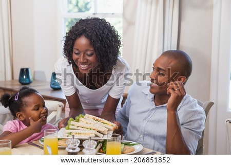 Mother serving sandwiches to her family at home in the kitchen - stock photo