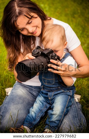Mother showing her baby photos on DSLR camera outdoors - stock photo