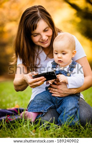 Mother showing her baby photos on smartphone - outdoor in nature - stock photo