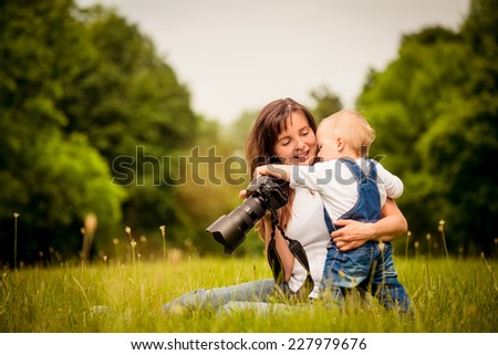 Mother showing her kid captured photos on dslr camera outdoor in nature - stock photo