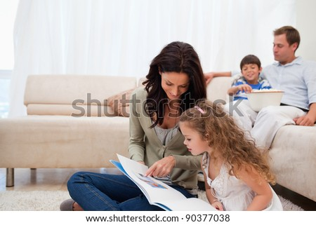 Mother showing photo album to her daughter - stock photo