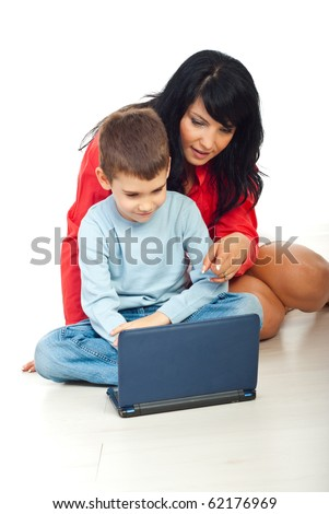 Mother showing something on notebook to his son and sitting together on floor in home - stock photo