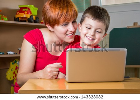 Mother showing something on the laptop to his son. - stock photo