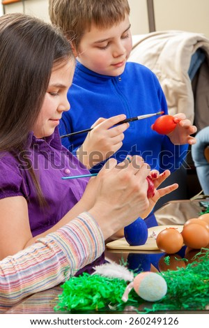 Mother showing to her children how to paint  Easter eggs - stock photo