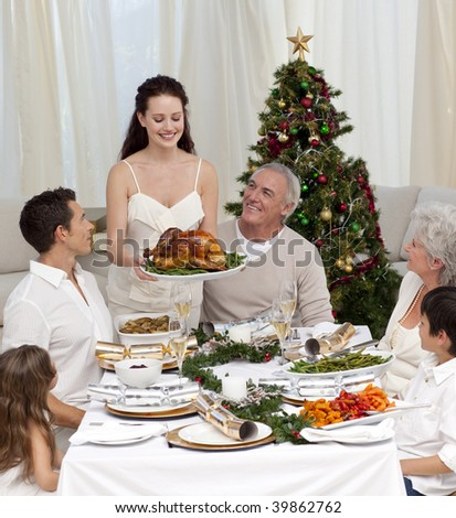 Mother showing turkey to her family for Christmas dinner - stock photo