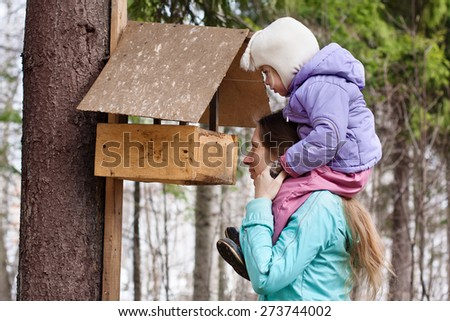 mother shows her daughter the bird feeder in the park - stock photo