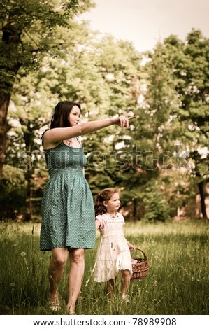 Mother shows with finger to her cute little daughter something interesting in distance - stock photo