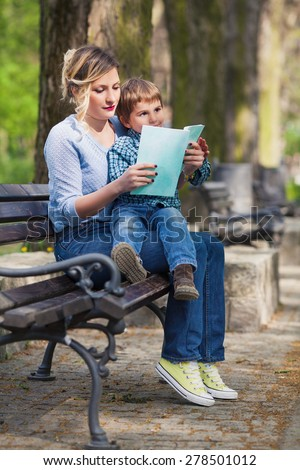 Mother sitting on a bench in a park and reading children??s stories to her son